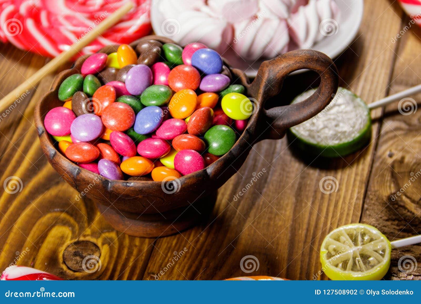 Bunter Knopf Formte Die Süßigkeiten, Die Mit Schokolade In Der Keramischen  Schüssel Auf Holztisch Gefüllt Wurden