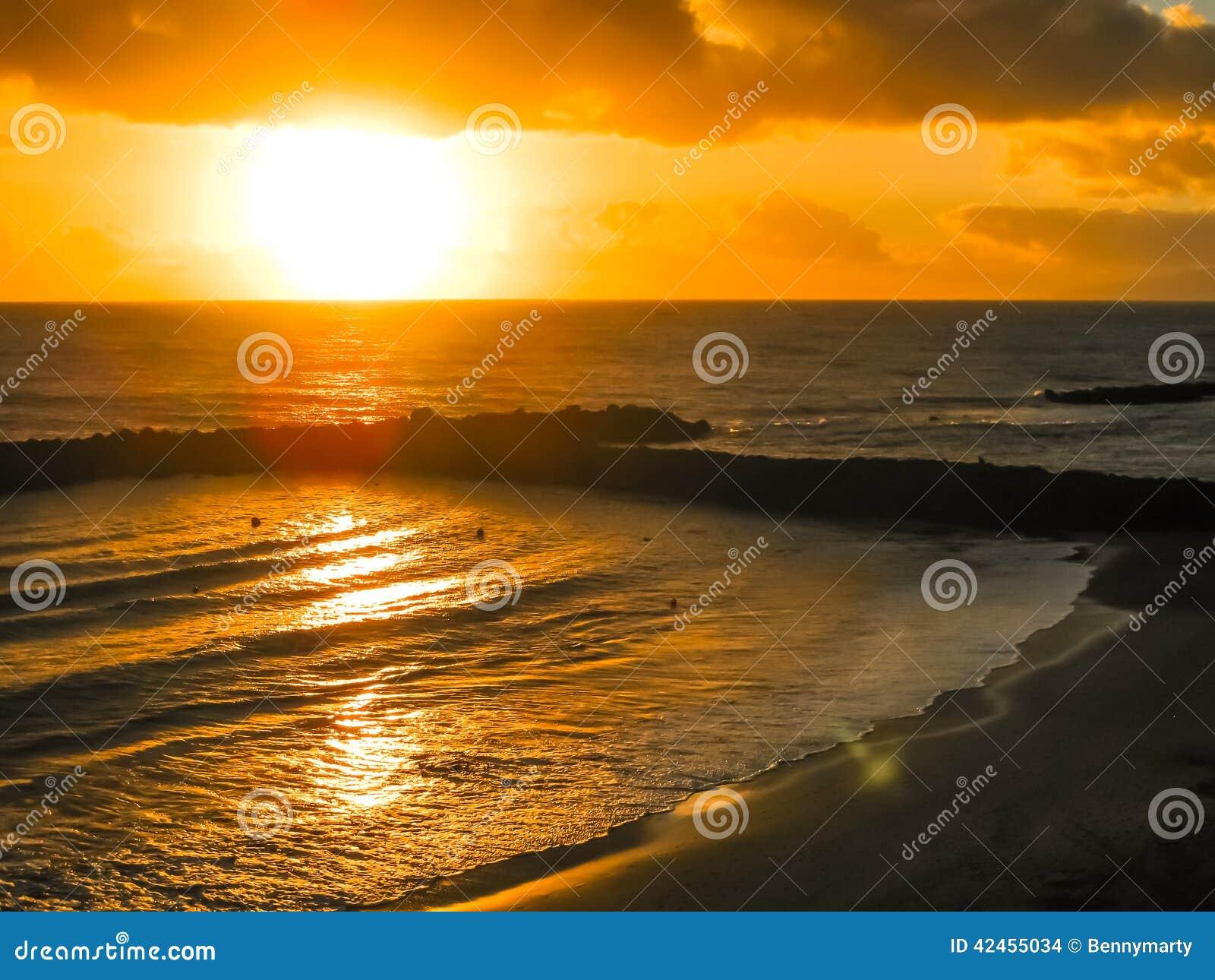 Bunter Sonnenuntergang durch den Ozean und den Strand