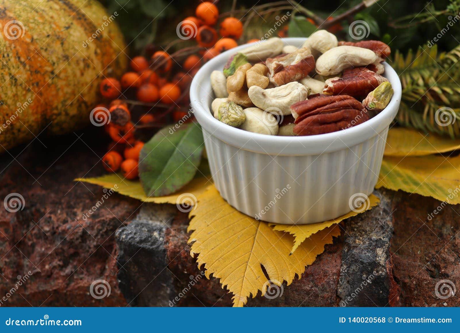Buntes Stillleben des Herbstes mit Blättern und Nüssen