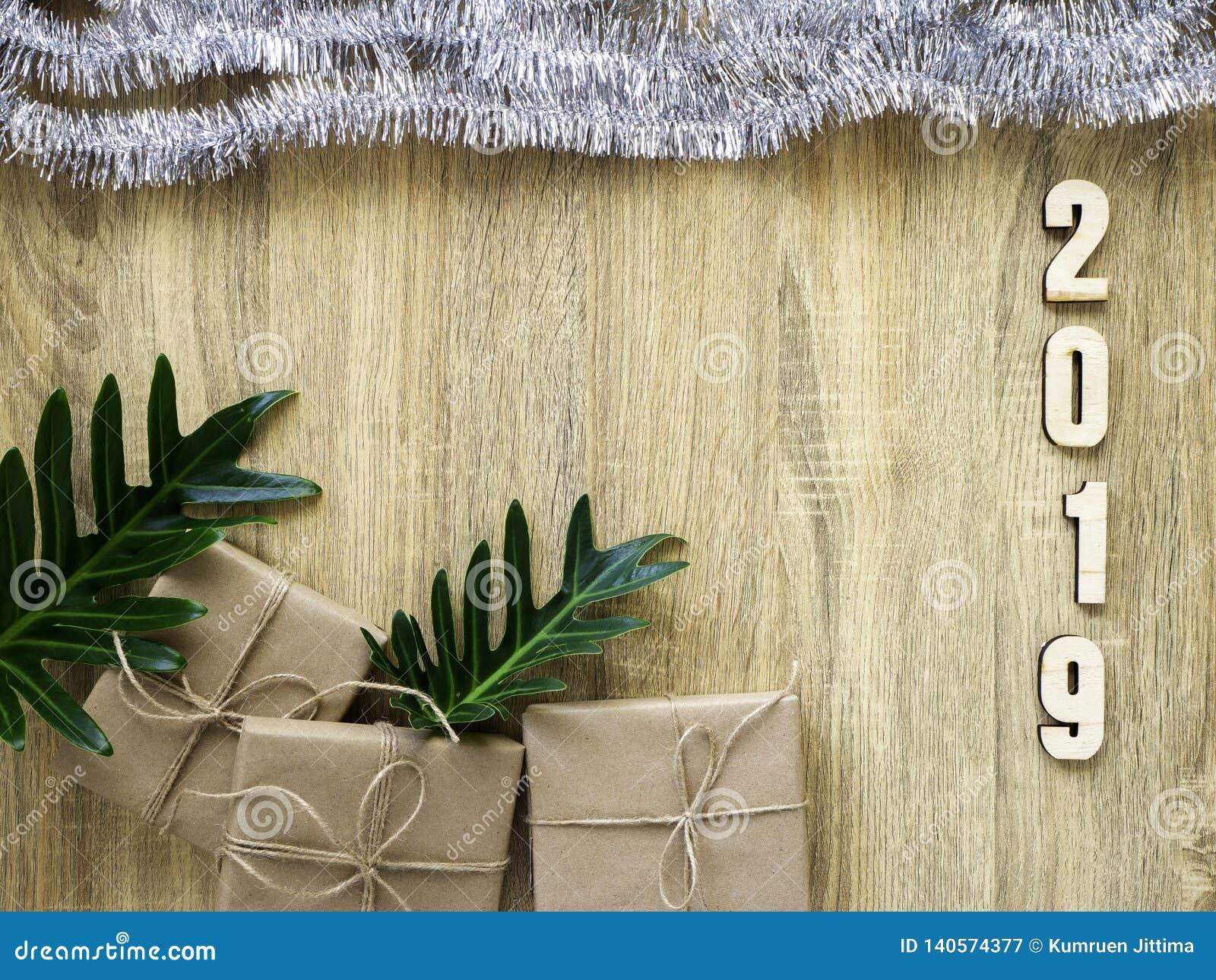Buon anno 2019 decorativo con il contenitore di regalo su di legno