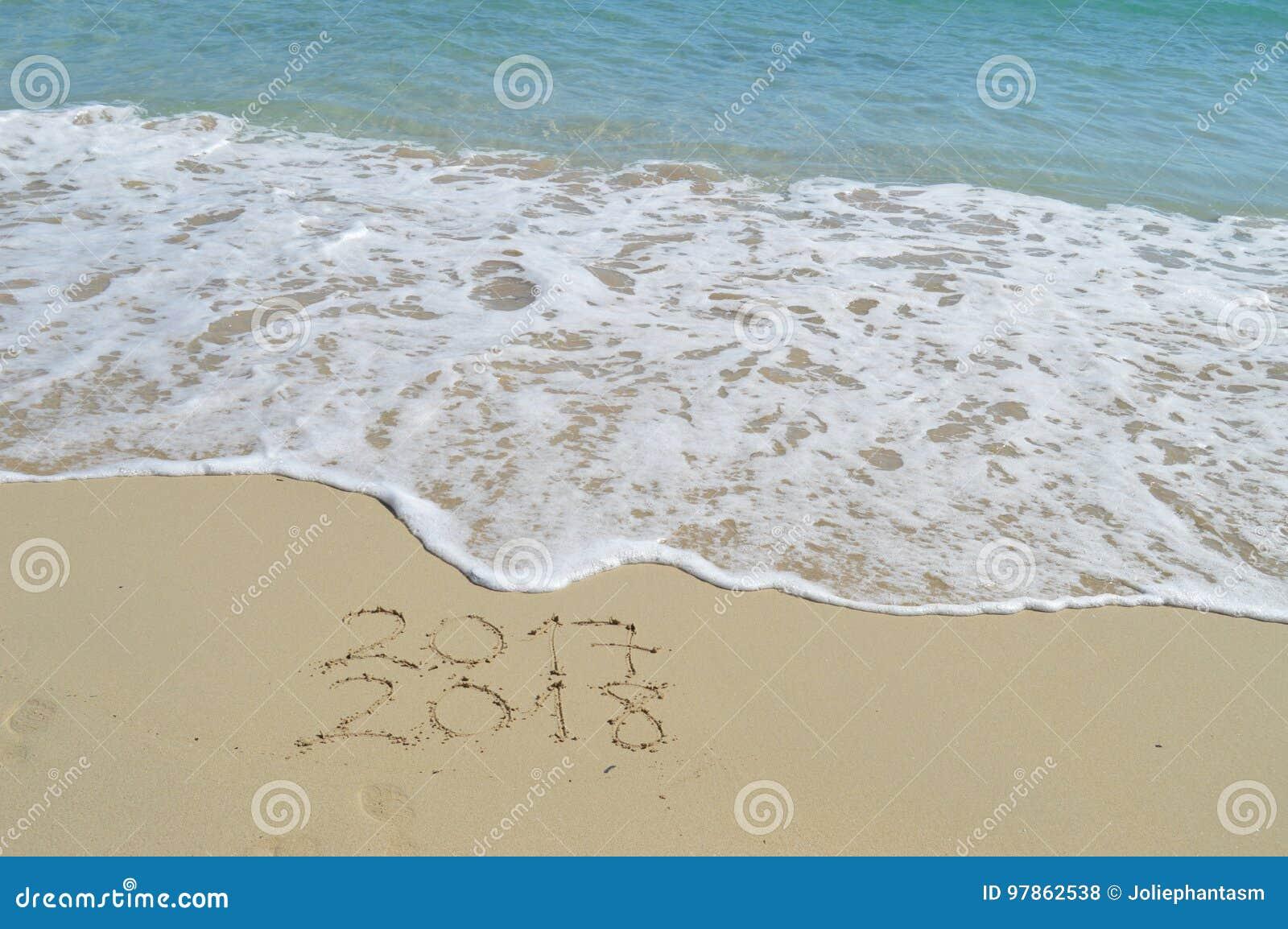 Buoni anni 2017 e 2018 scritti a mano sulla sabbia