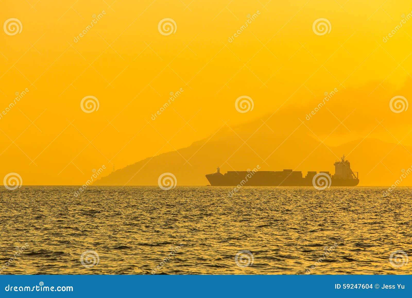 Buque de carga en el mar en la puesta del sol