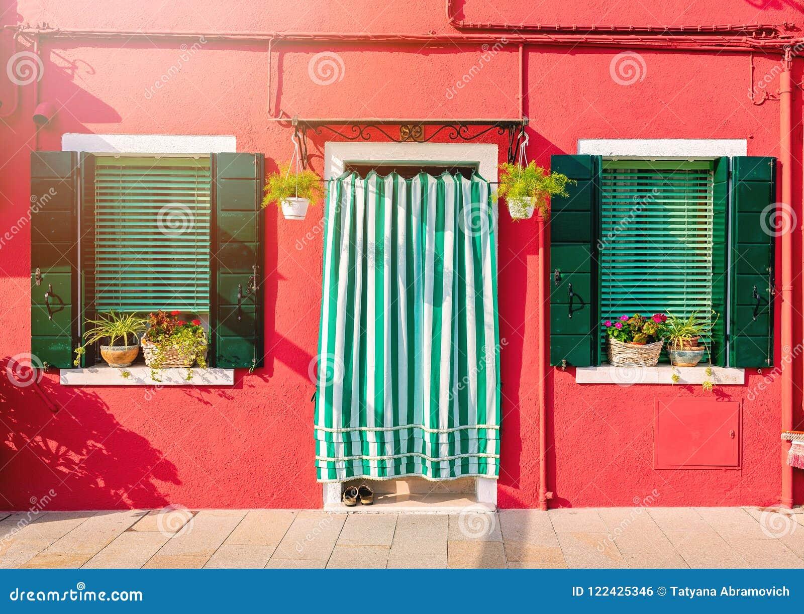 BURANO, WŁOCHY - 2 Wrzesień, 2016 Pomarańczowy dom z dwa okno i drzwi Dekorujący z kwiatami Typowy widok