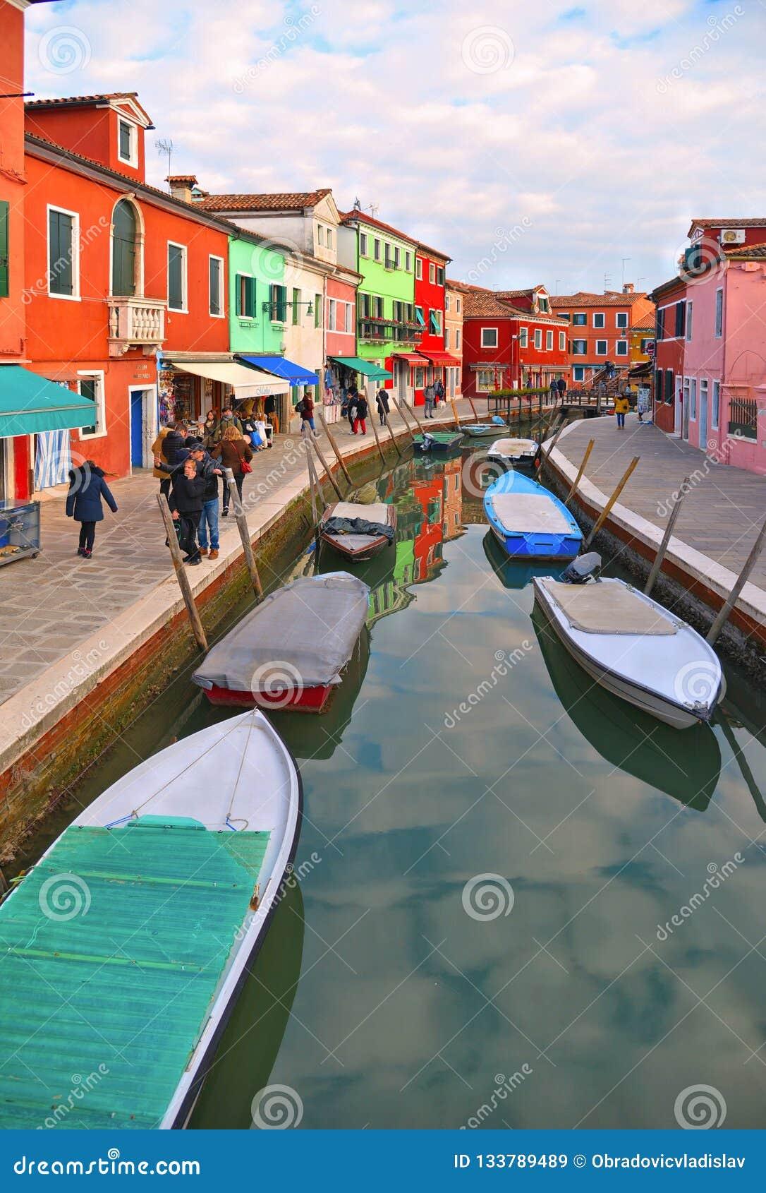 Burano wyspy malownicza ulica z małymi barwionymi domami w rzędzie, wodny kanał z fishermans łodziami, chmurny niebieskie niebo