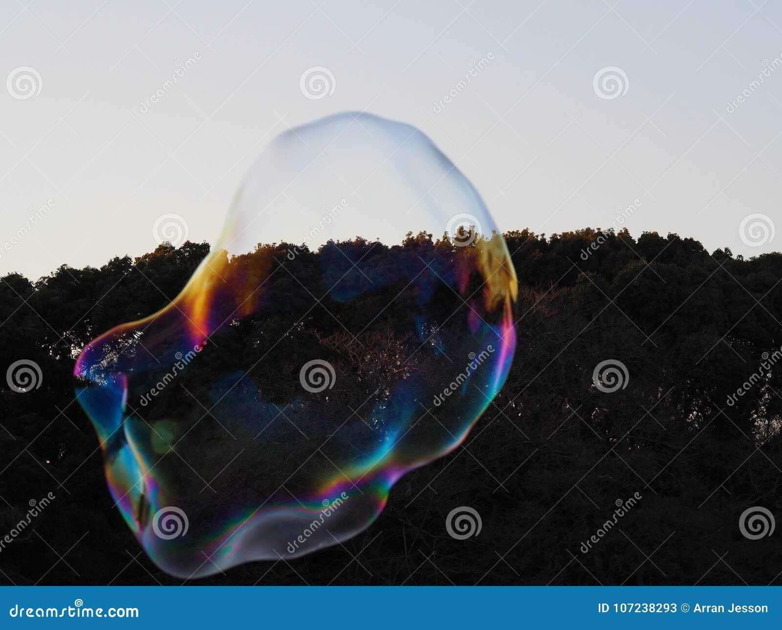 Burbuja enorme que refleja un arco iris de colores, puesto en contraste por el bosque oscuro detrás de él y estallar alrededor