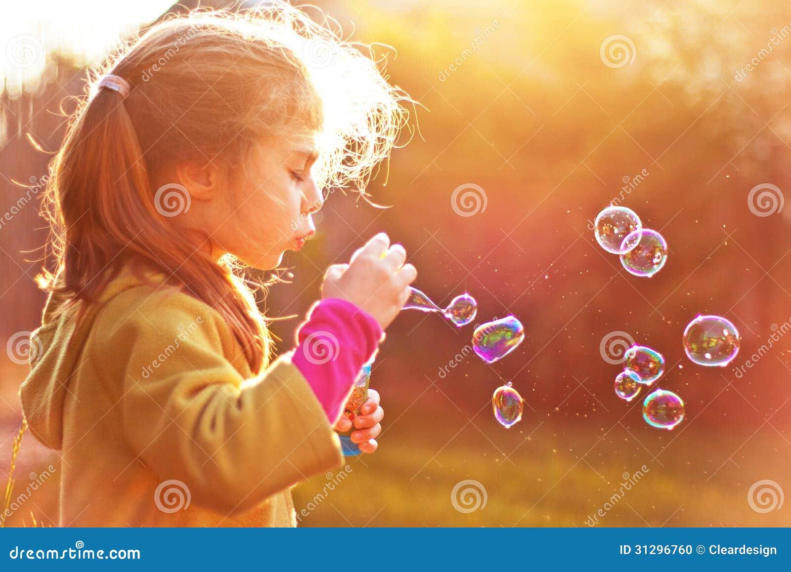 Burbujas de jabón de la muchacha del niño que soplan al aire libre