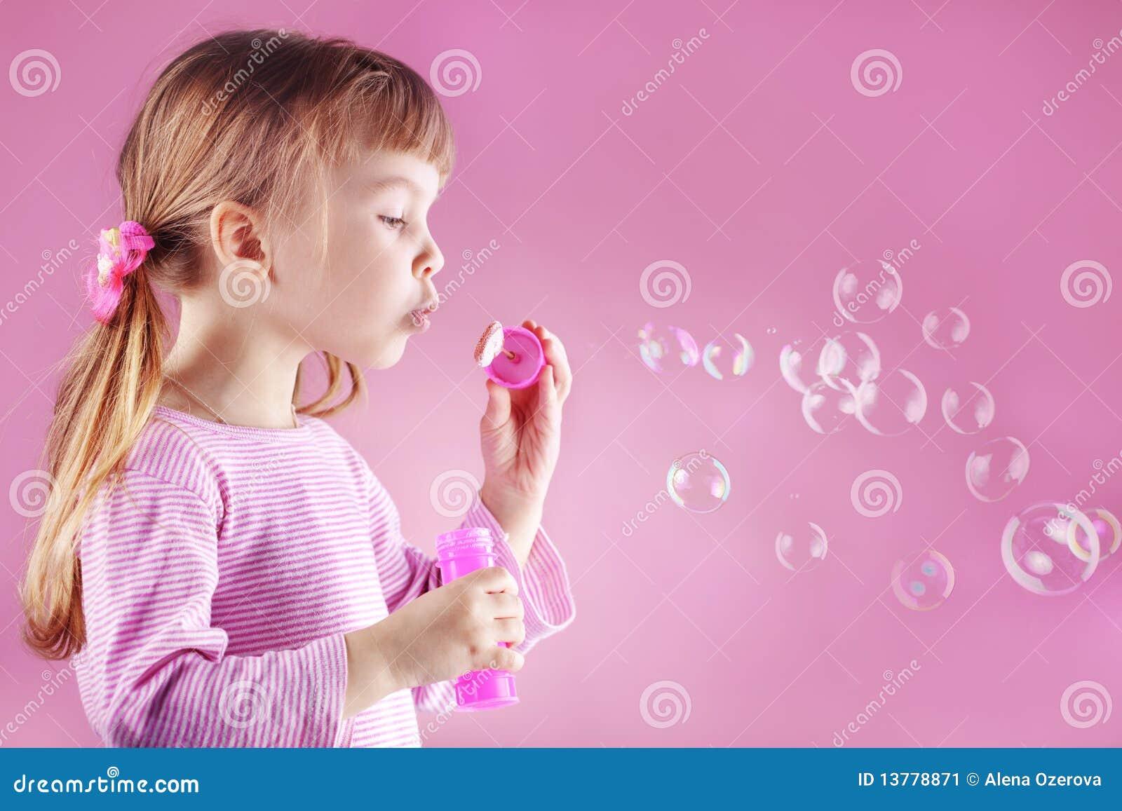 Burbujas de jabón de la muchacha que soplan