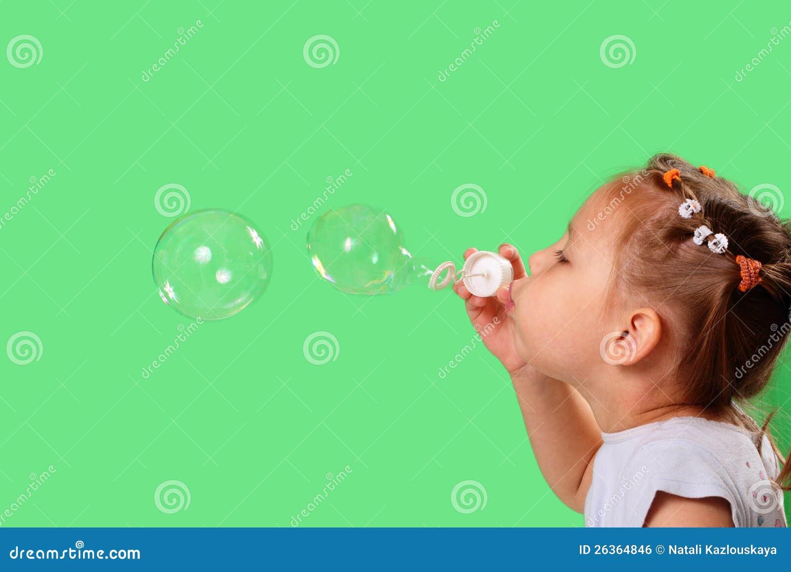 Burbujas de jabón de la niña que soplan