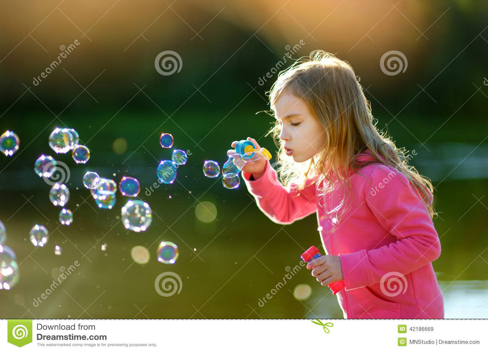 Burbujas de jabón de la niña que soplan preciosa divertida