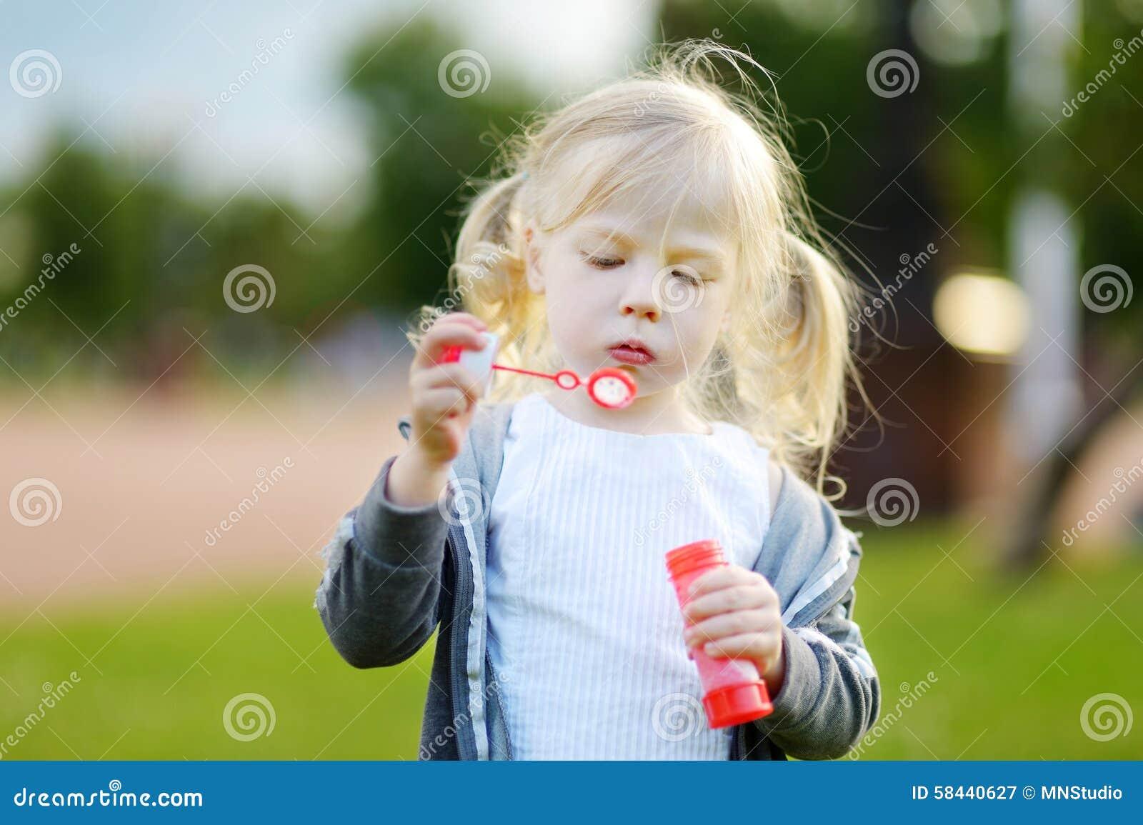 Burbujas de jabón de la niña que soplan preciosa divertida al aire libre