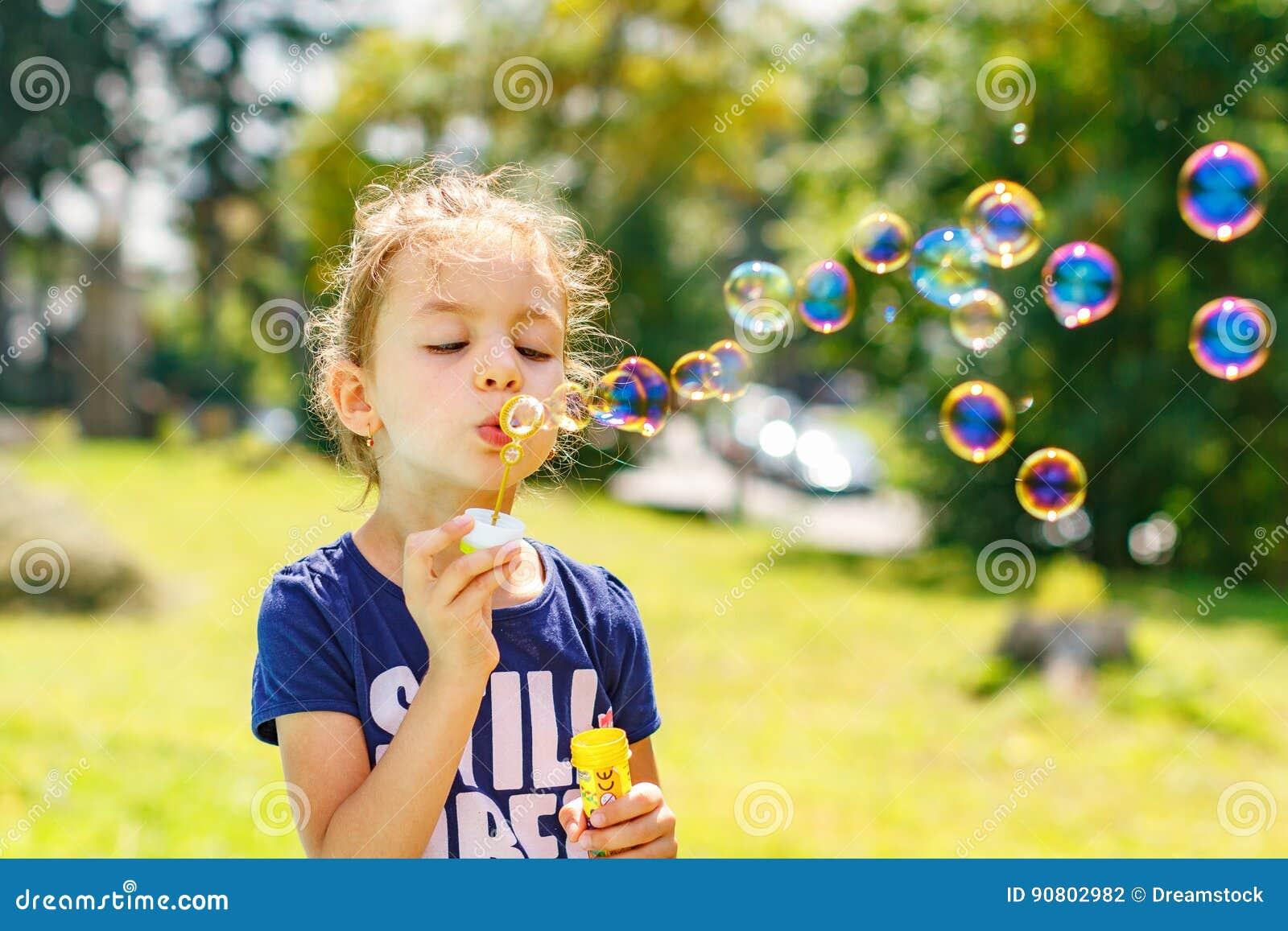 Burbujas de un jabón de la niña que soplan en parque del verano