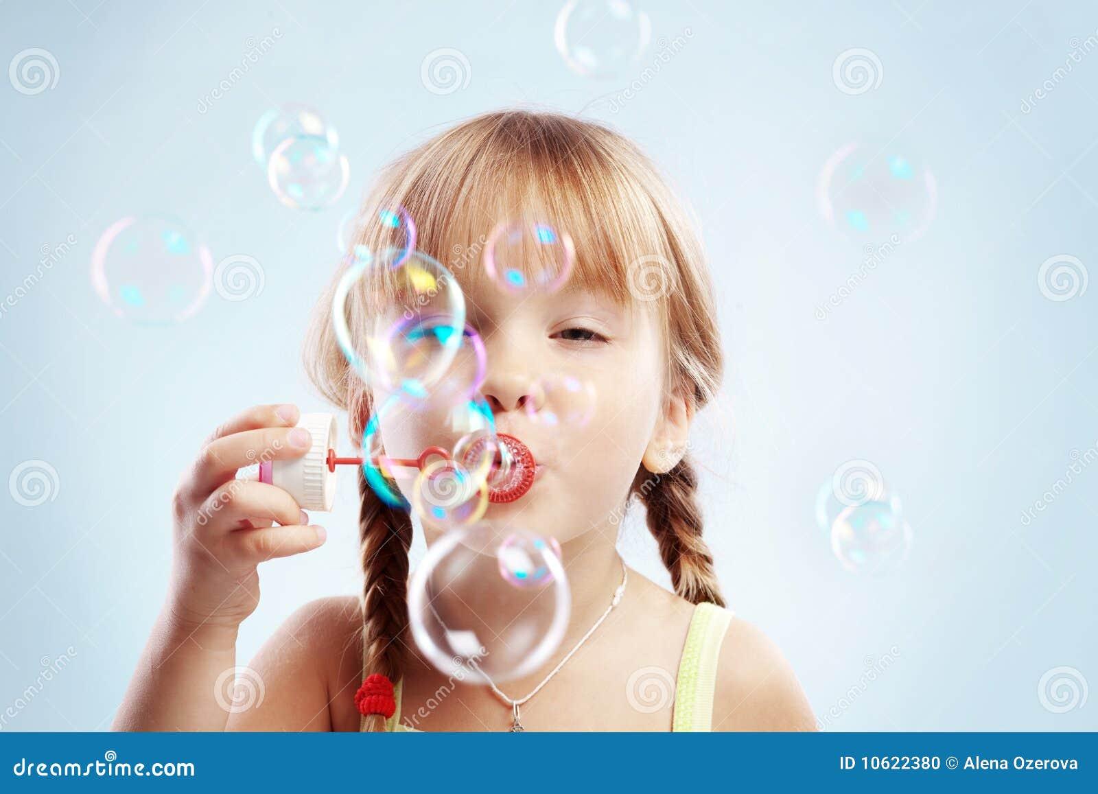 Burbujas que soplan de la niña