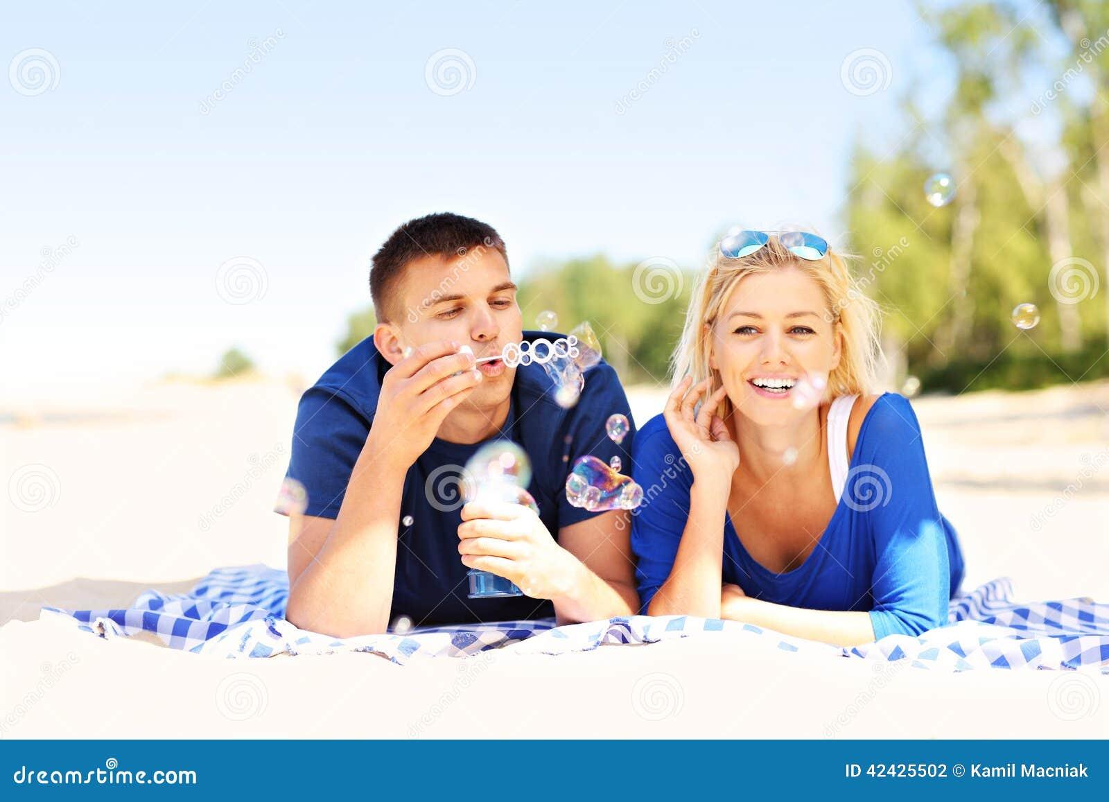 Burbujas que soplan de los pares felices en la playa