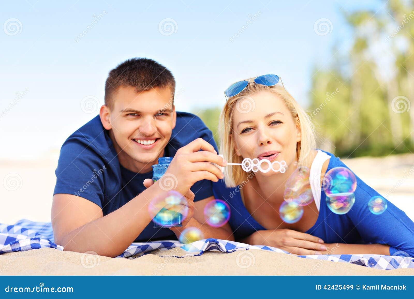 Burbujas que soplan de los pares jovenes en la playa