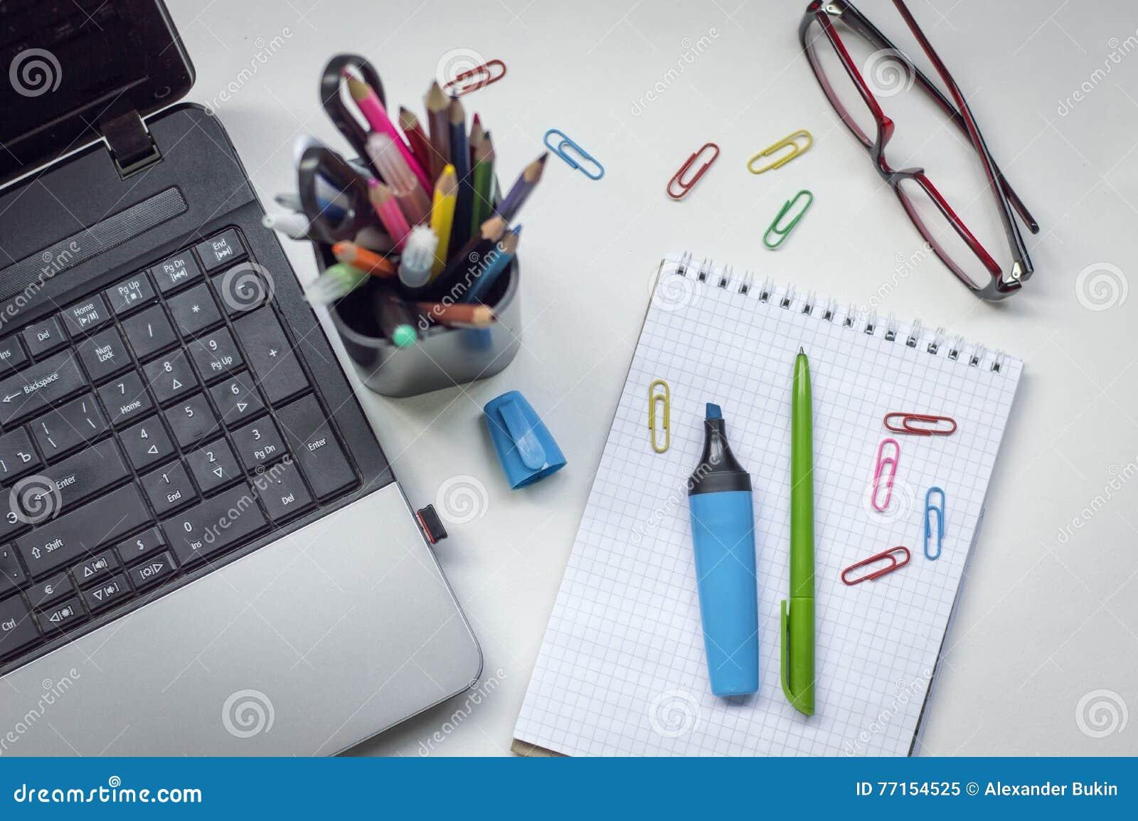 Bureau avec un ordinateur portable, un carnet et des marqueurs