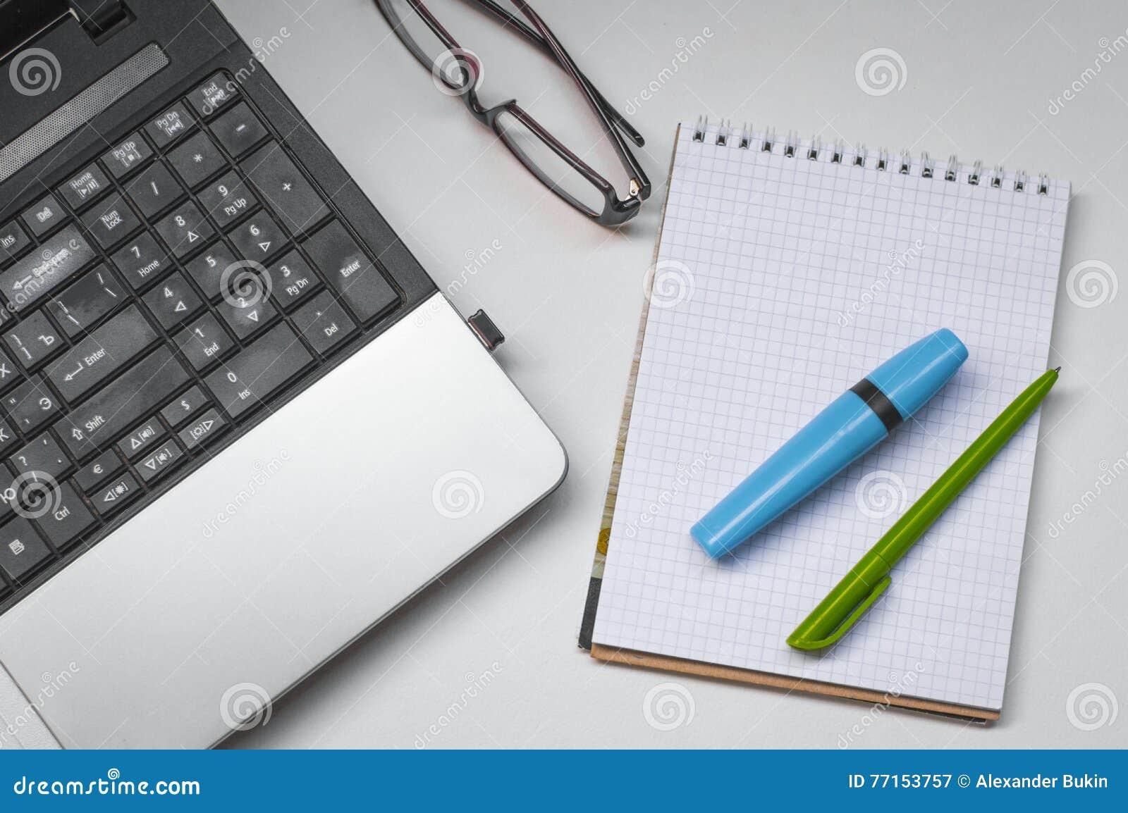 Bureau avec un ordinateur portable, un carnet et le stylo avec un marqueur