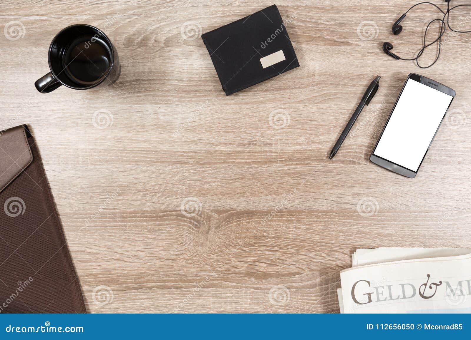 Bureau en bois avec le smartphone, écouteurs, stylo, portefeuille, tasse de café