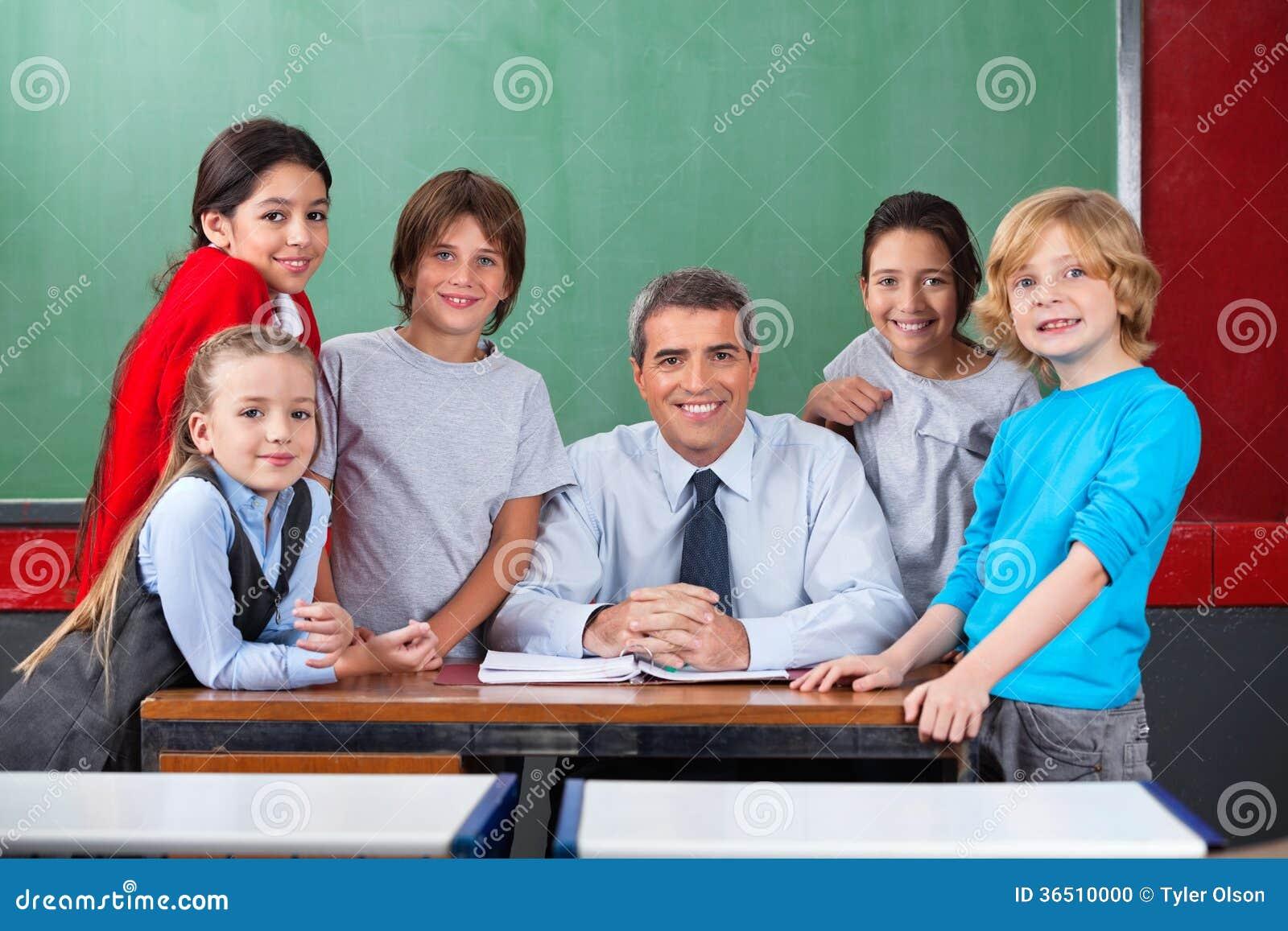 Bureau sûr de With Schoolchildren At de professeur masculin
