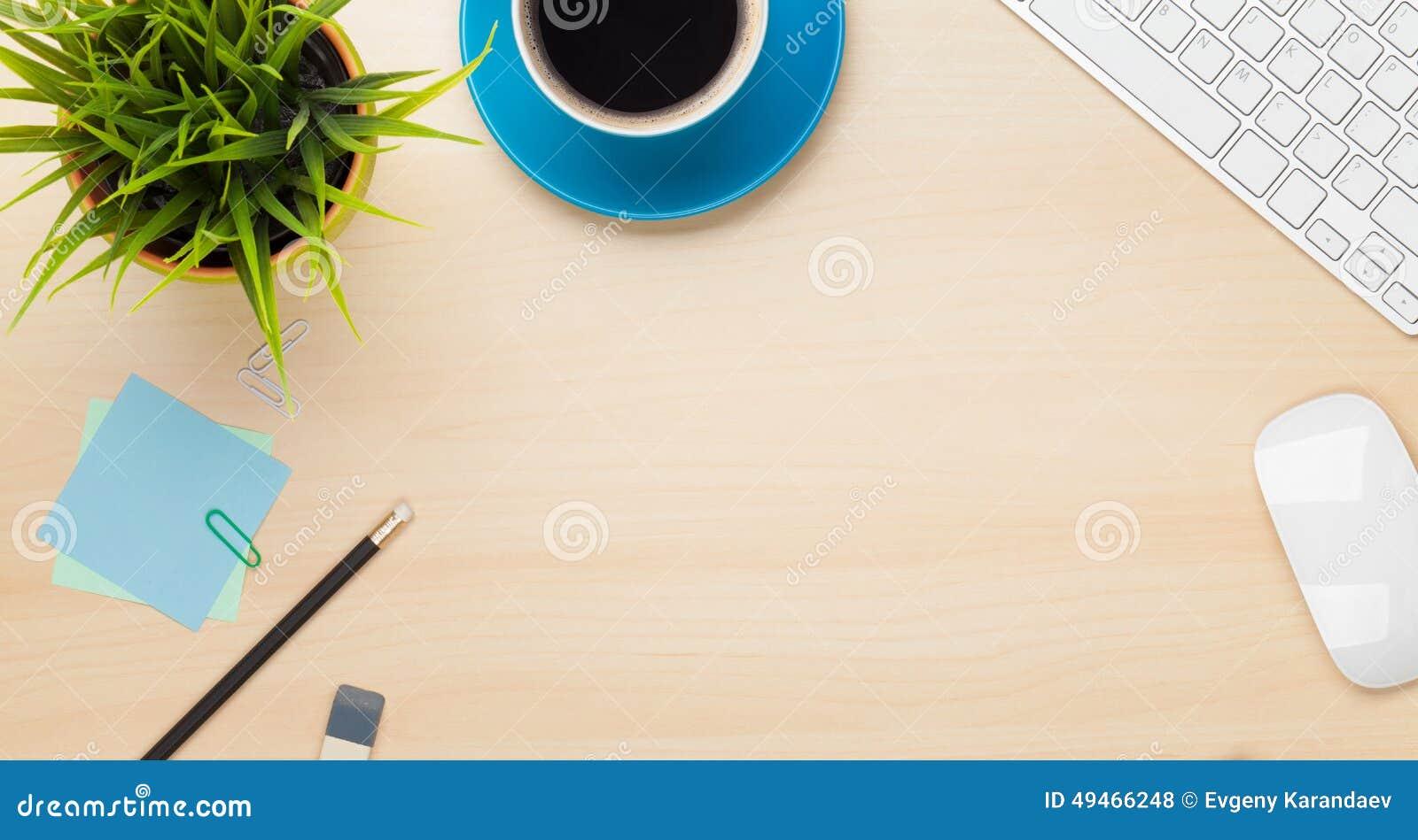 Bureaulijst met koffiekop, computer en bloem