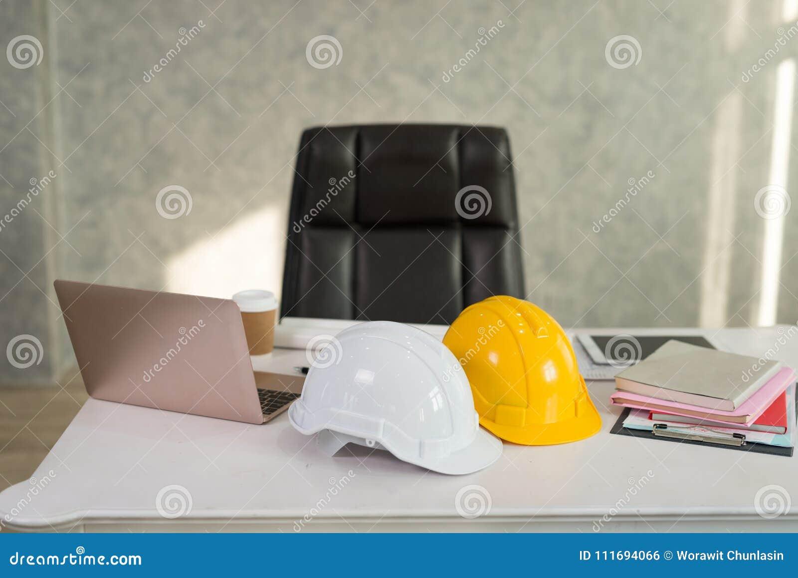 Bureaus van ingenieurs met laptops, veiligheidshelm, digitale tablet