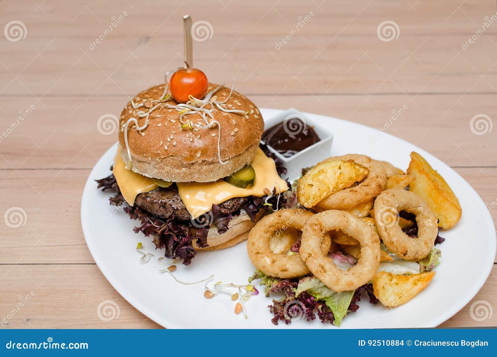 Burger με τα τηγανητά και τα δαχτυλίδια κρεμμυδιών