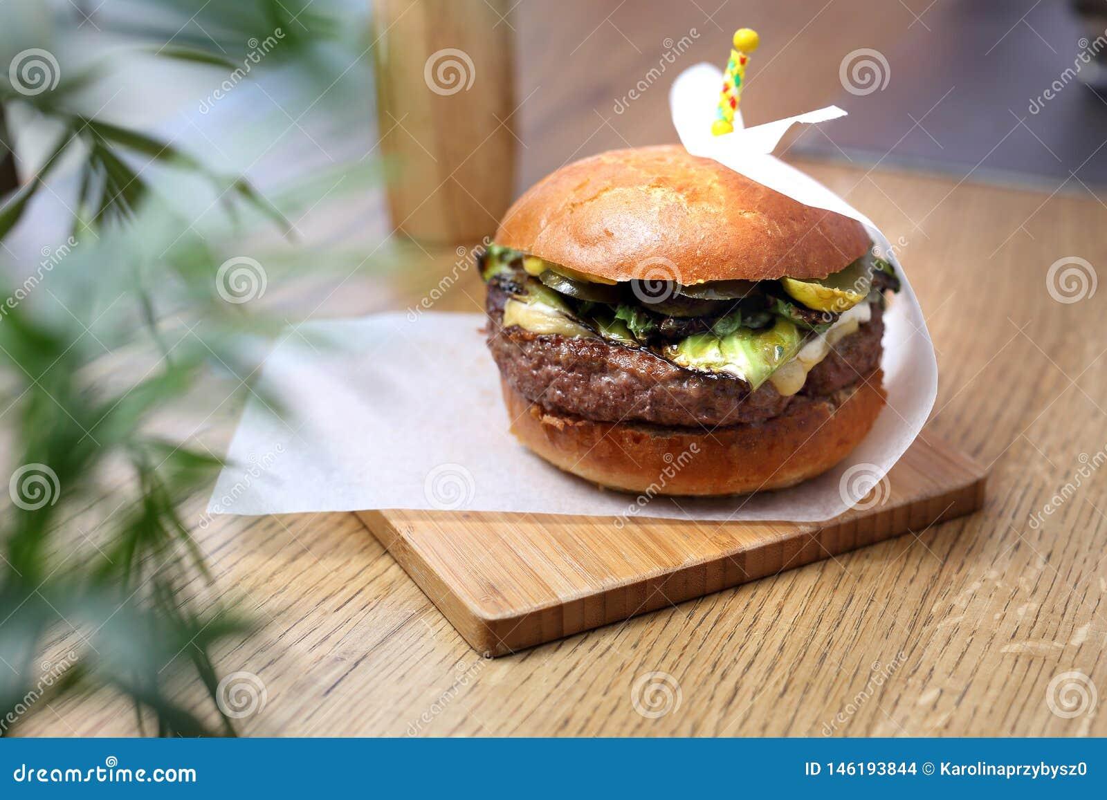 Burger με cutlet βόειου κρέατος με την πράσινη σαλάτα και τα ψημένα στη σχάρα πράσινα λαχανικά