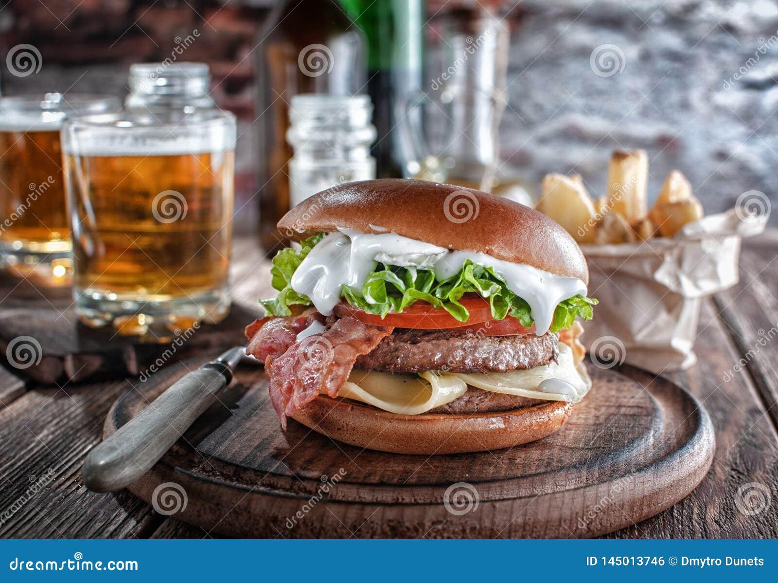 Burger πιάνων με το μπέϊκον και cutlet με το τυρί, ντομάτα, πράσινα