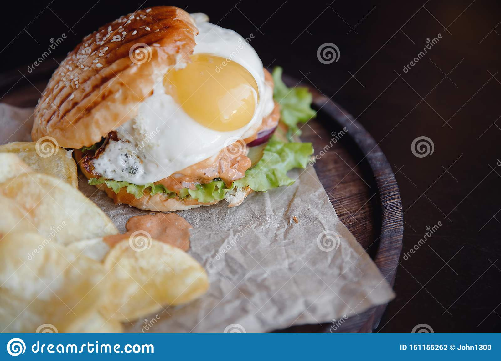 Appetizing Burger With Fried Egg Meat Patty Grilled Bun Near Potato Chips Concept Fast Food Stock Photo Image Of Board Cheeseburger 151155262