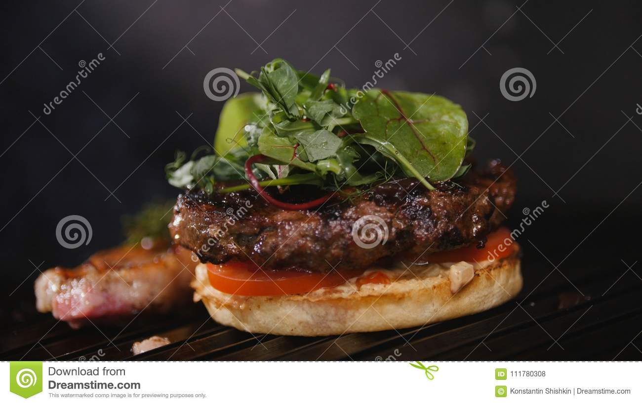 Burger, frying the bun on the grill, putting the tomatoes, meat and sauce