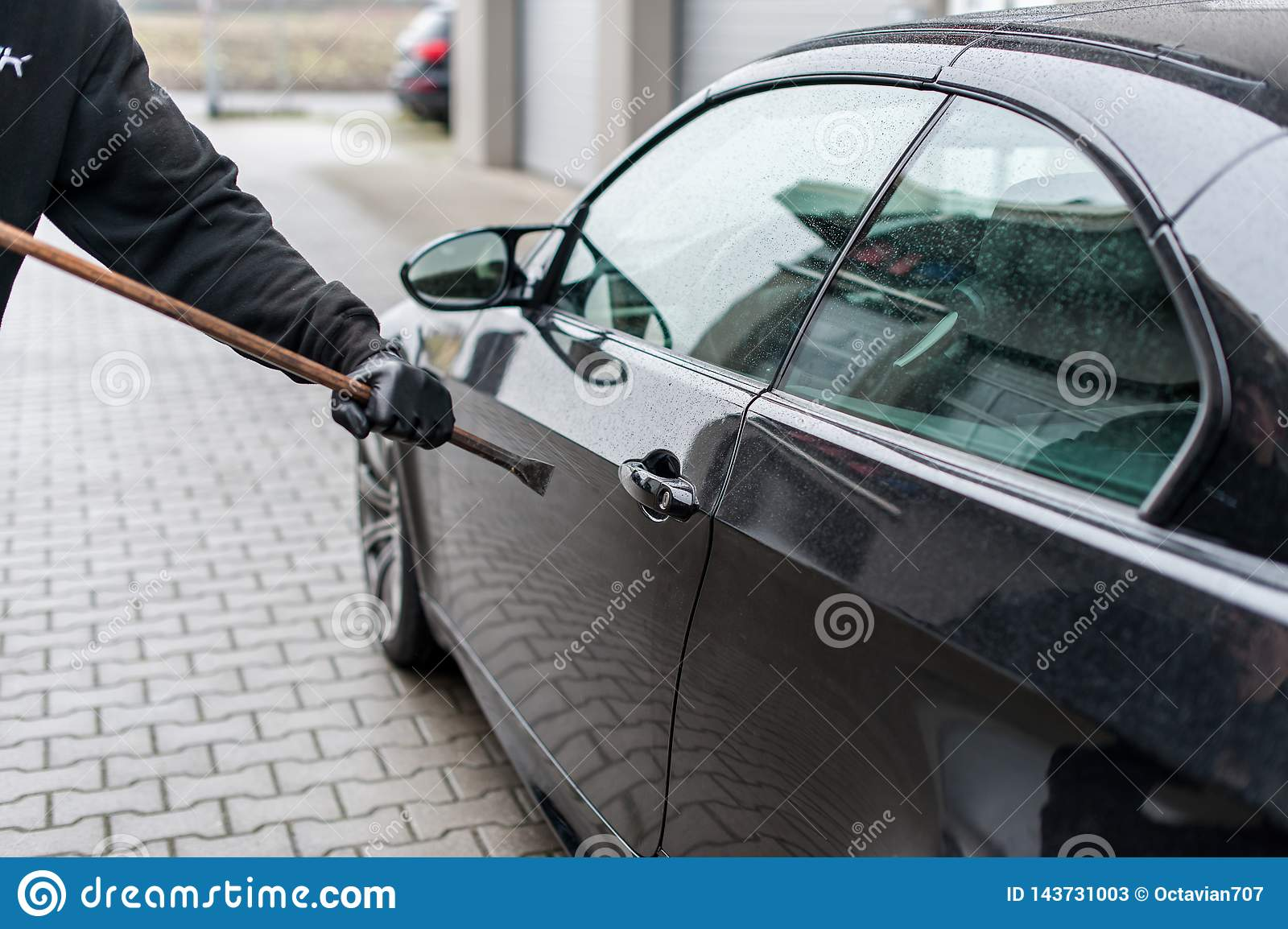 Burglar with gloves try to open a car