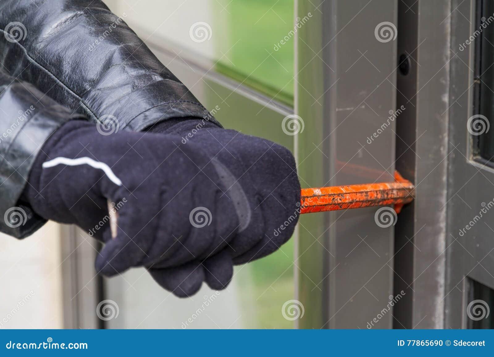 Burglar wearing leather coat breaking in a house