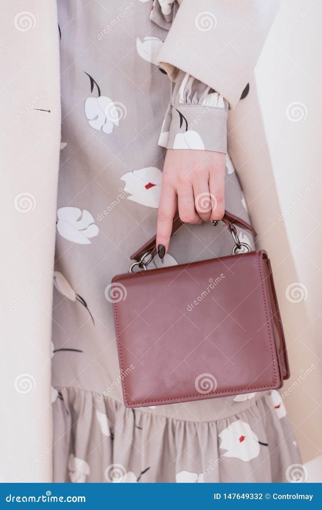 Burgunder-Tasche in der Hand