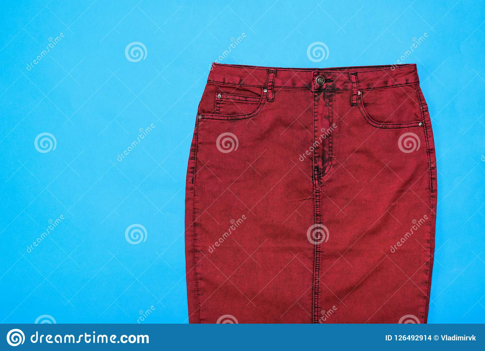 c4a8f4326 Burgundy denim skirt on blue background. Stylish women`s denim clothing.  Front view.