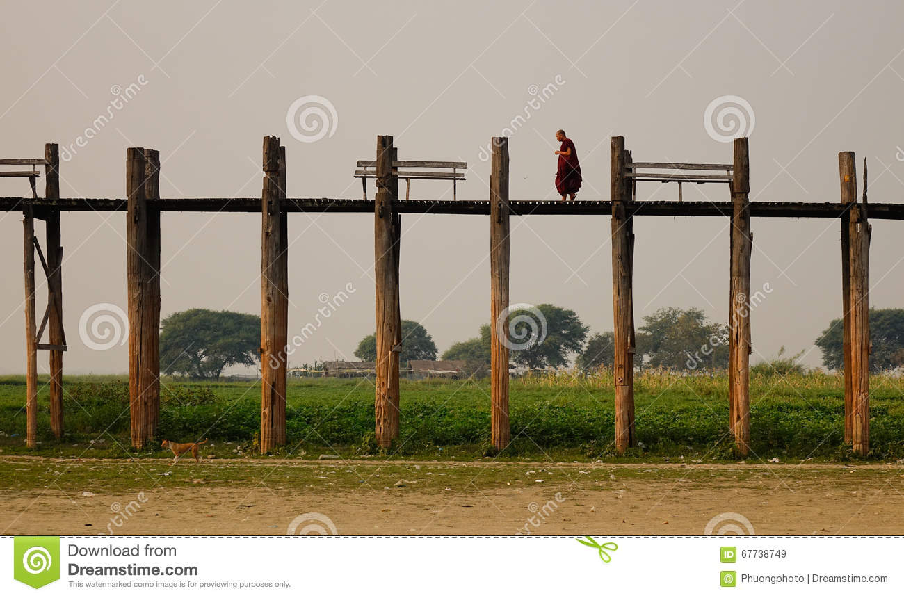 Burmese monk in red clothes walking on Ubein Bridge