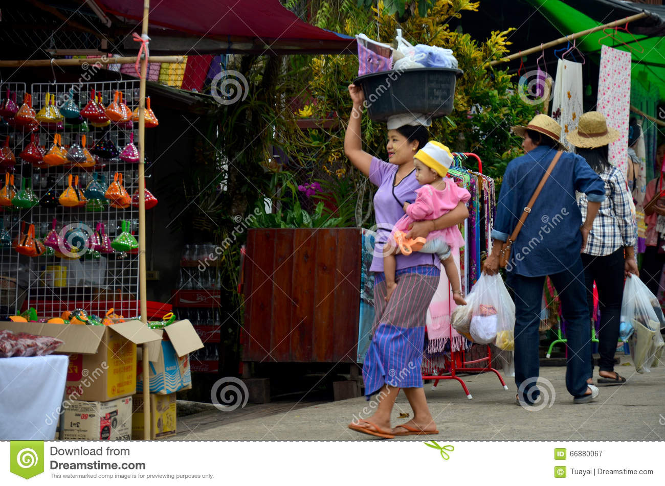 Burmese Mother hold the baby and carrying basin plastic on her h