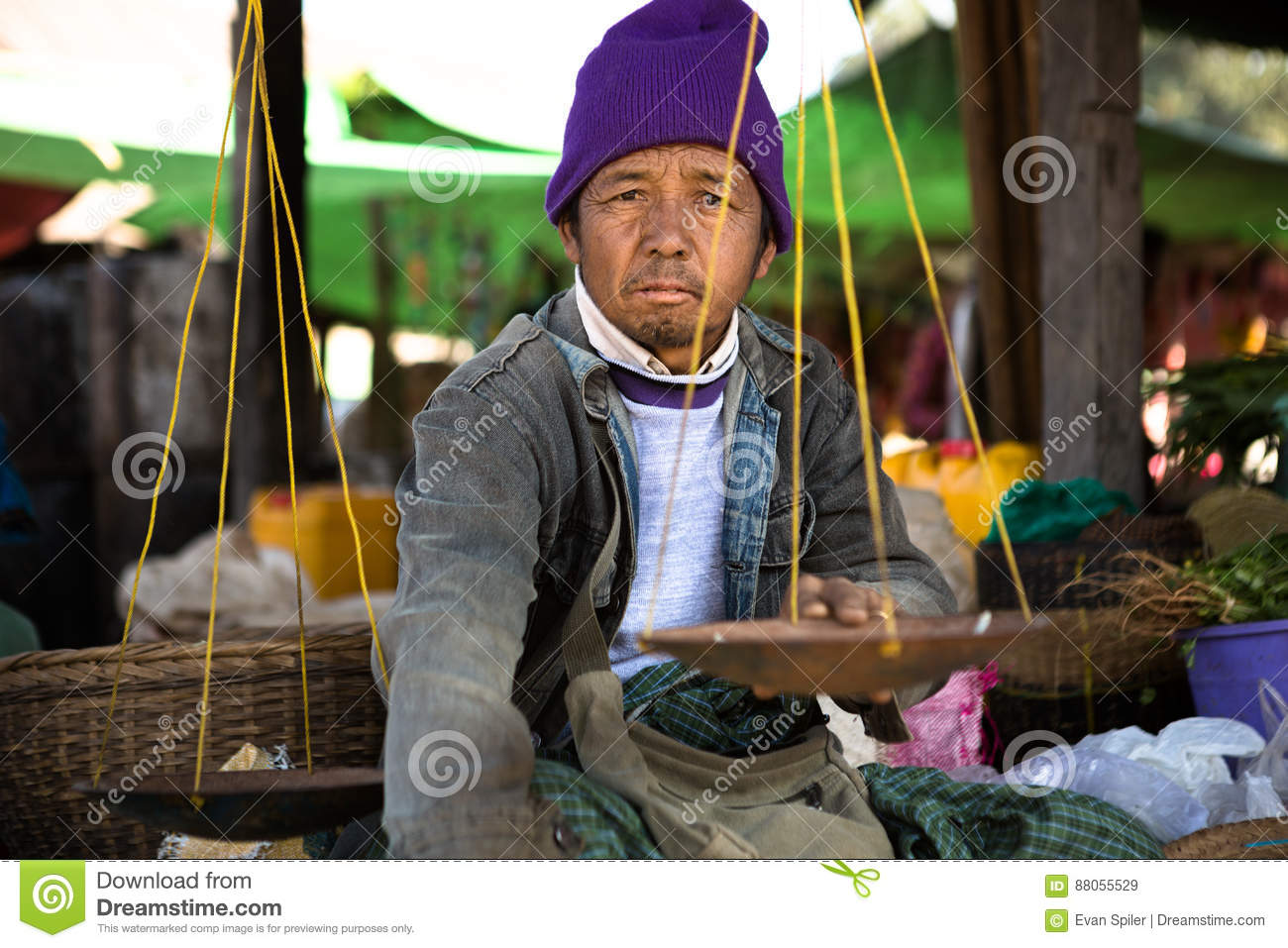 Burmese Vendor In Purple Hat Holds A Scale Used To Measure