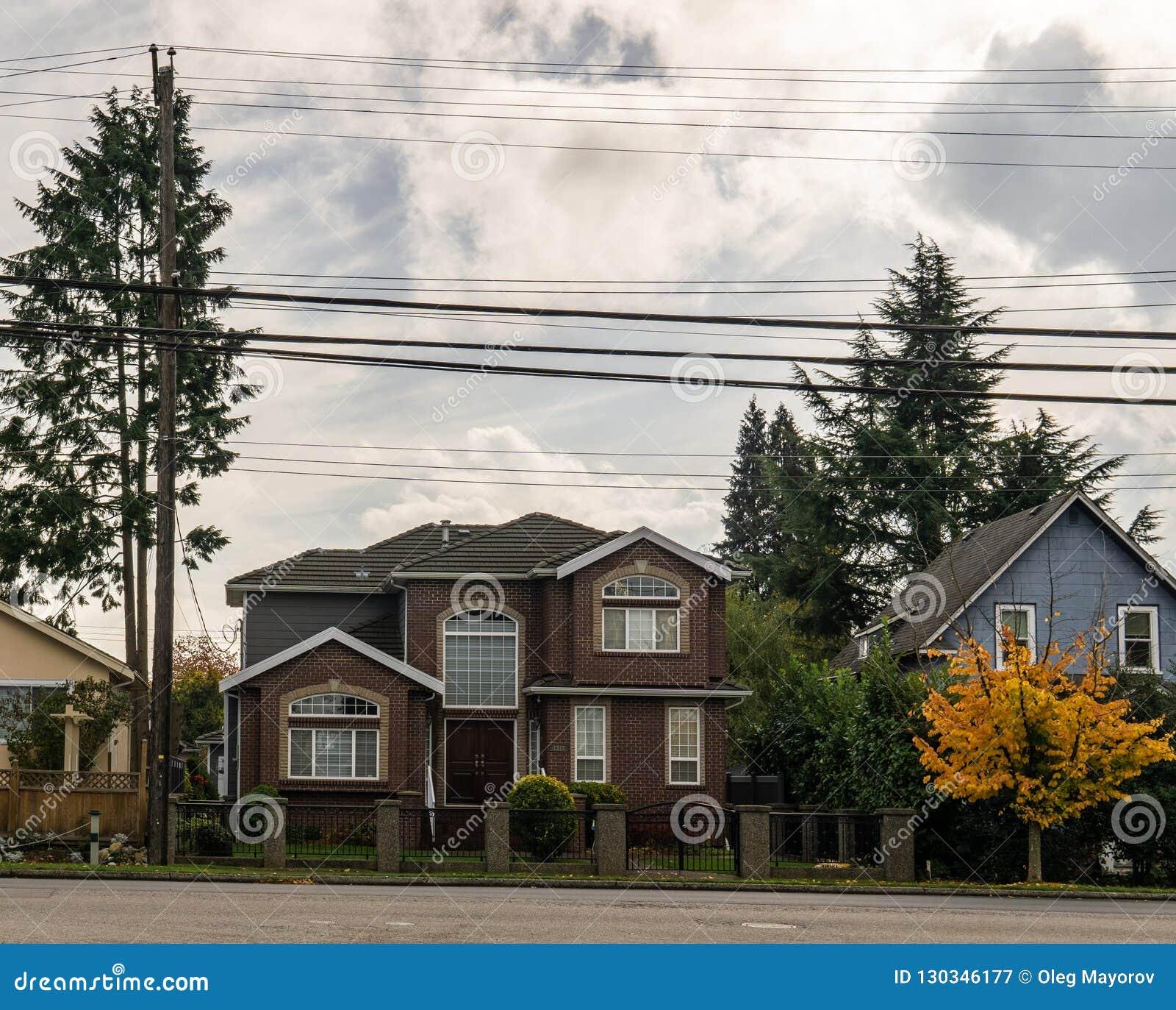 BURNABY, CANADÁ - 24 de outubro de 2018: Casa na área residencial com as árvores amarelas e vermelhas no outono