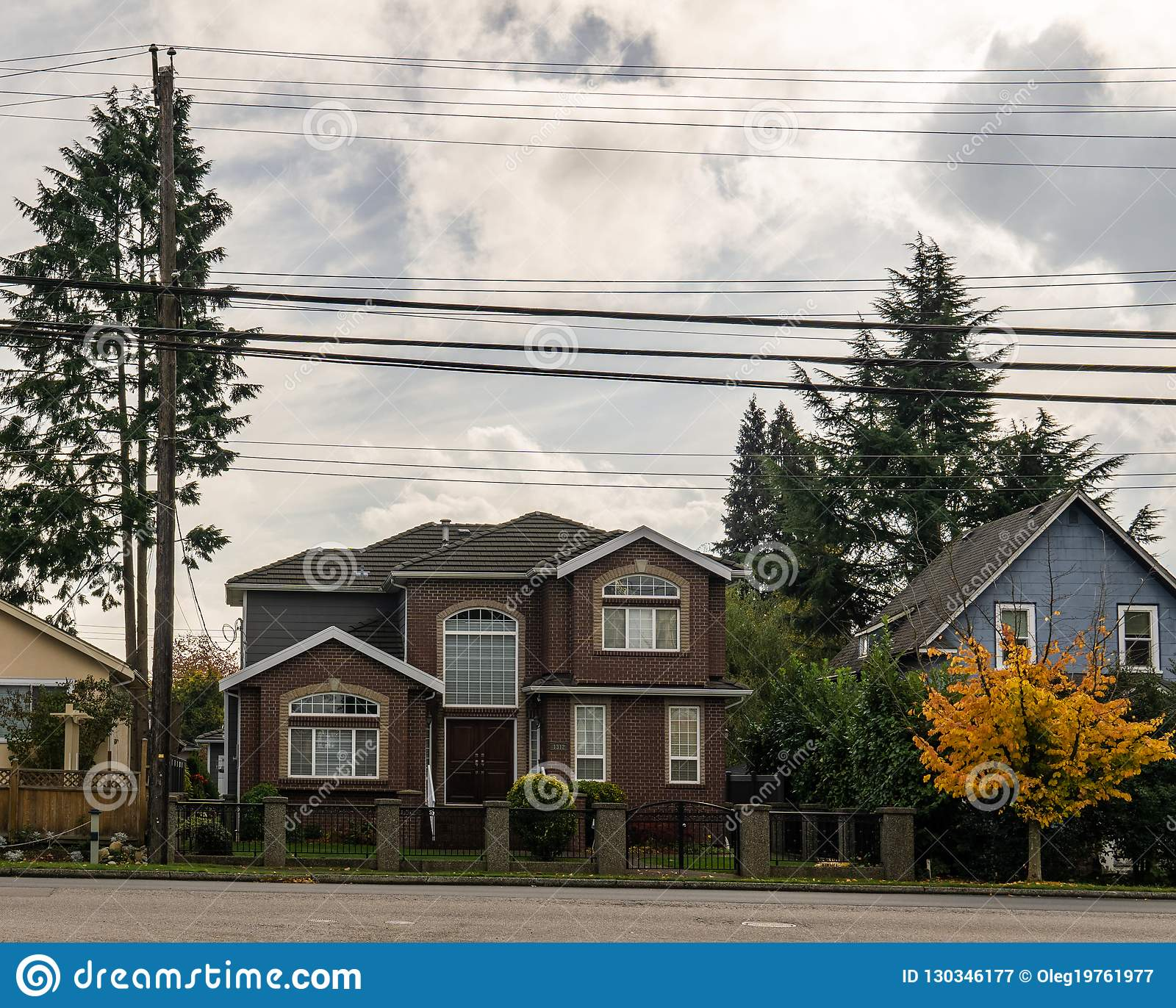 BURNABY, CANADA - October 24, 2018: House in residential area with yellow and red trees in autumn.