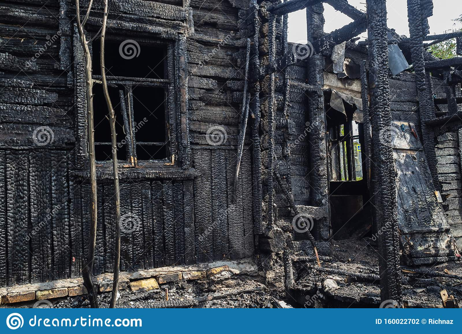 Burned Down To Coals Of A Wooden House  Black House From Fire Stock Photo