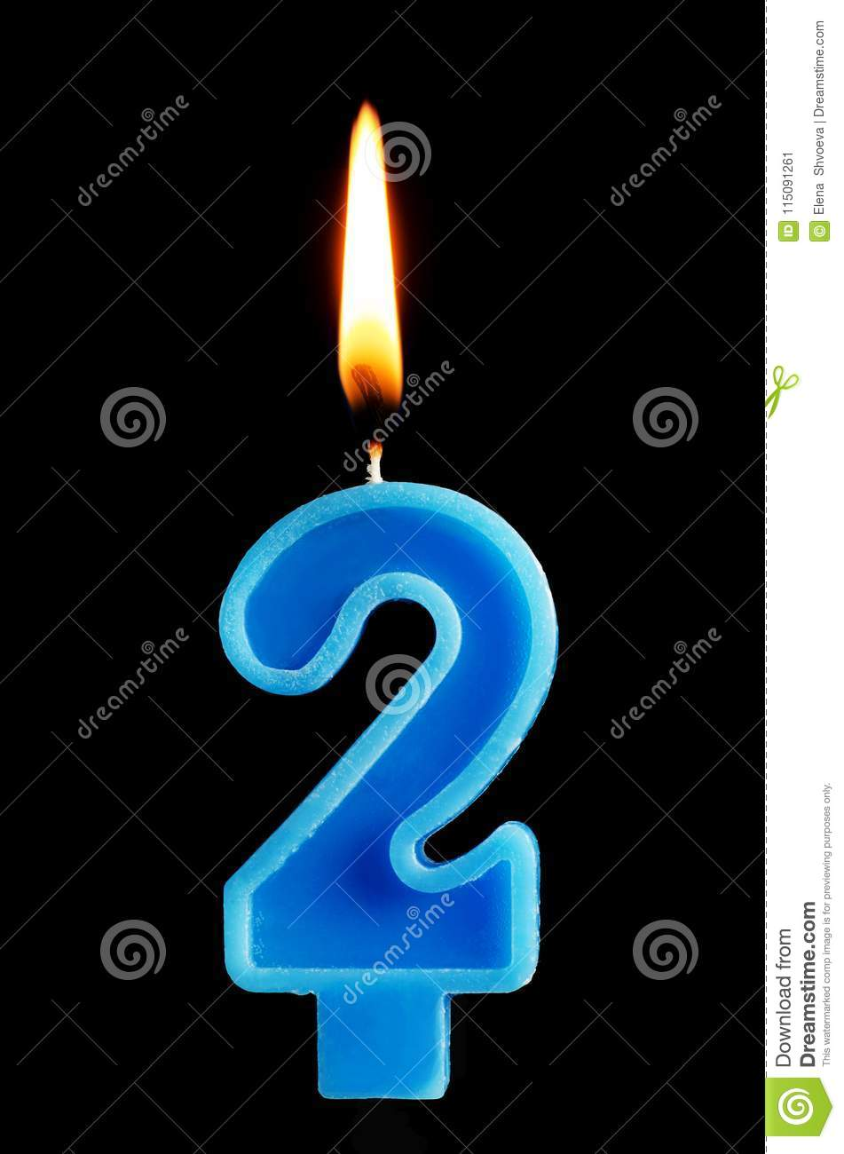 Burning birthday candle in the form of 2 two figures for cake isolated on black background. The concept of celebrating a birthday,