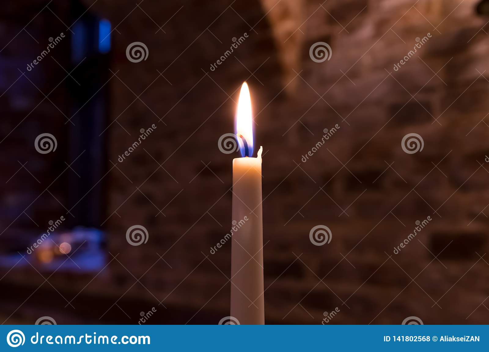 A burning candle against the wall of a brick