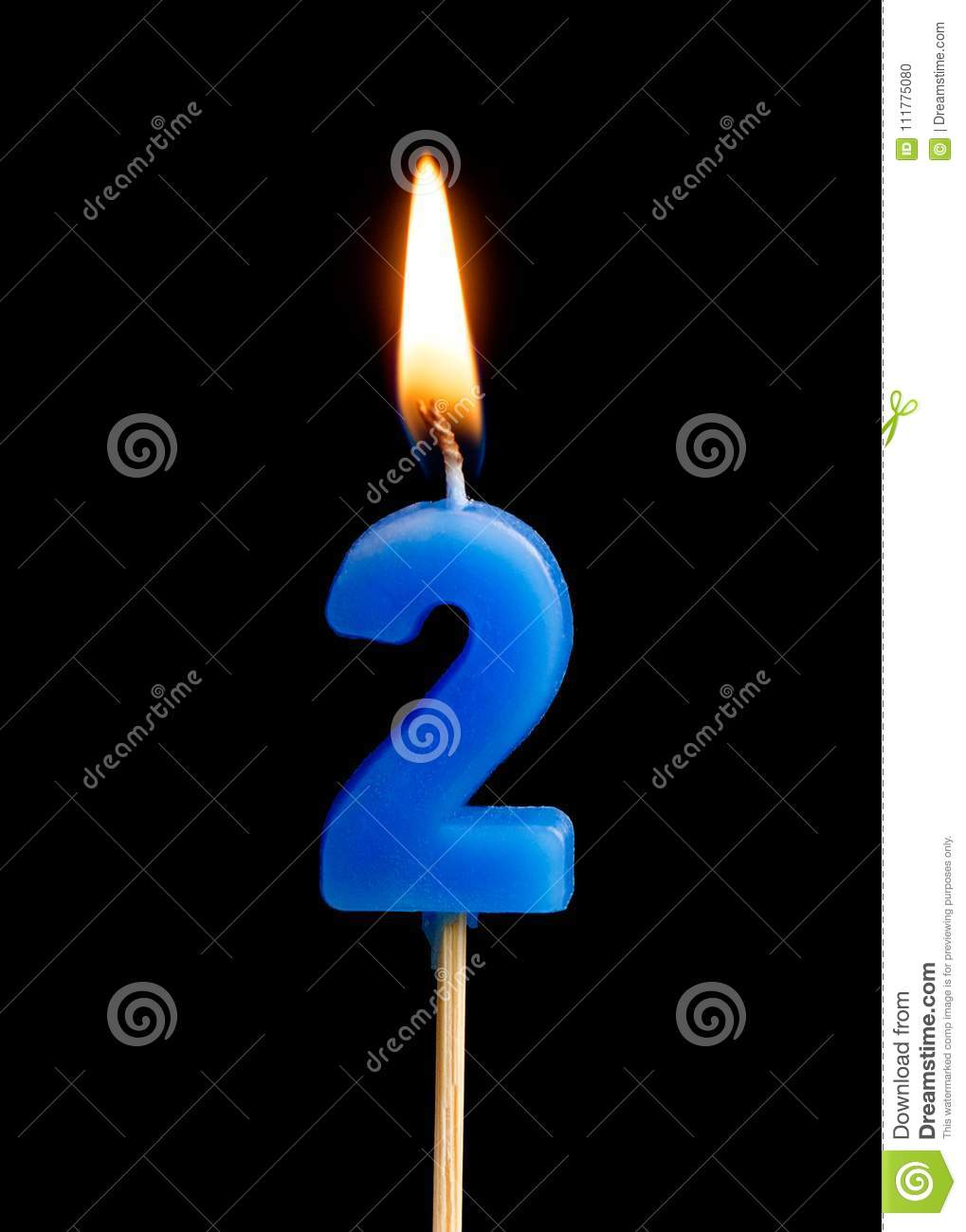 Burning candle in the form of two figures numbers, dates for cake isolated on black background.