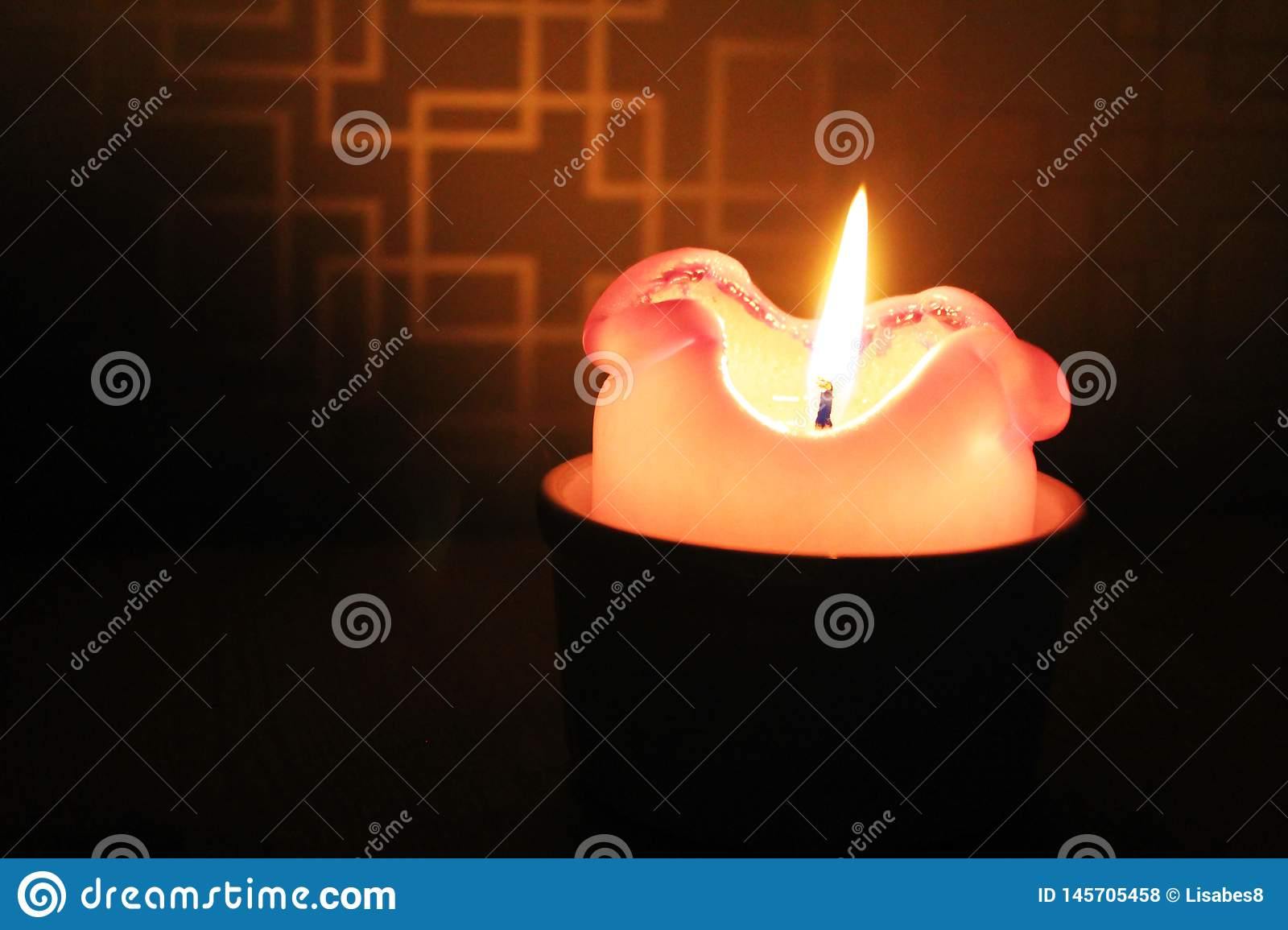 Burning candle on a dark blured background