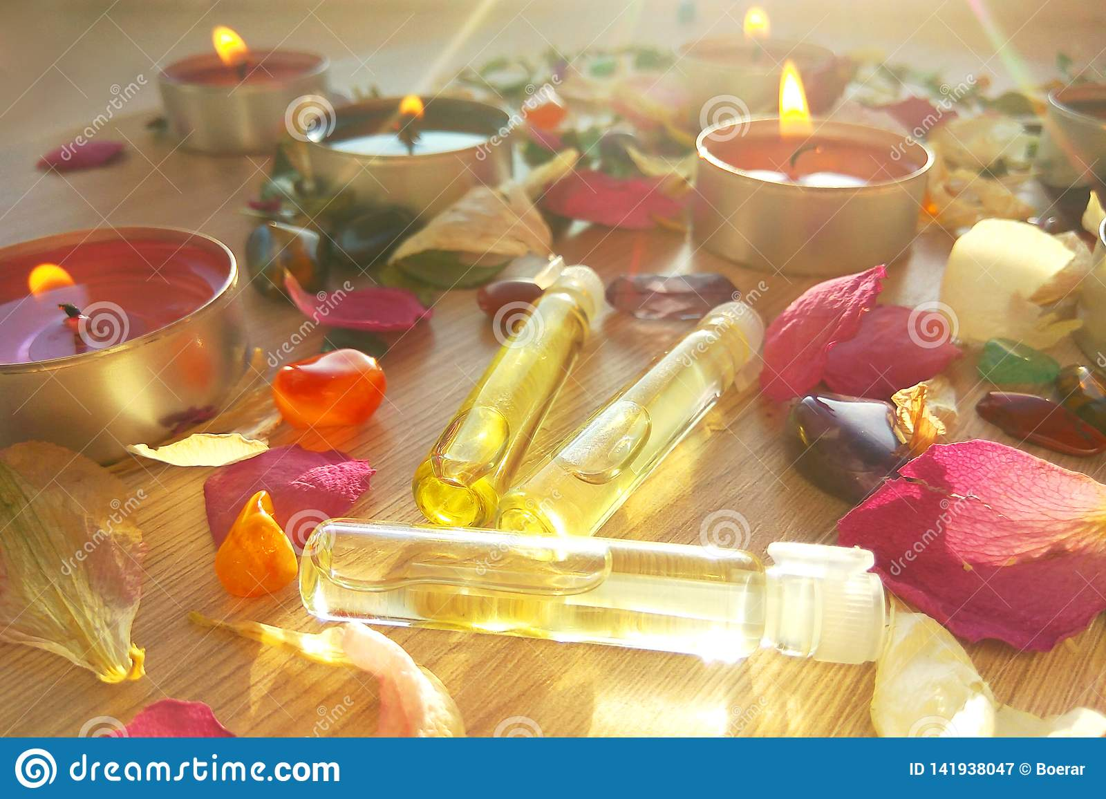 Burning candles with essential spa oil, rose flower petals and colorful gems on wooden background
