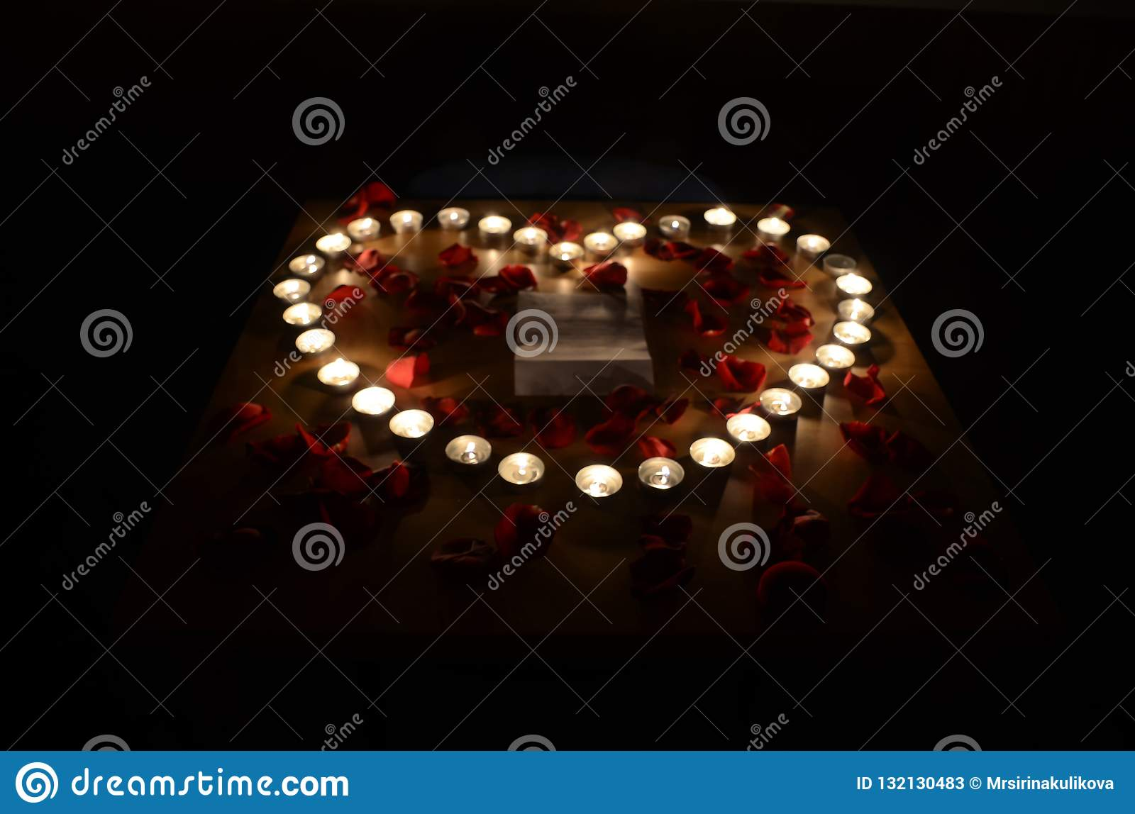 Burning candles in heart form surrounded by red rose petals in t