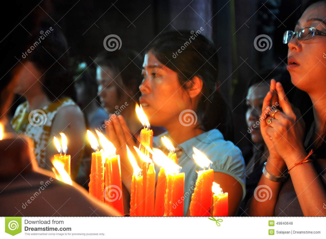 Burning candles and praying people in a Vietnamese pagoda