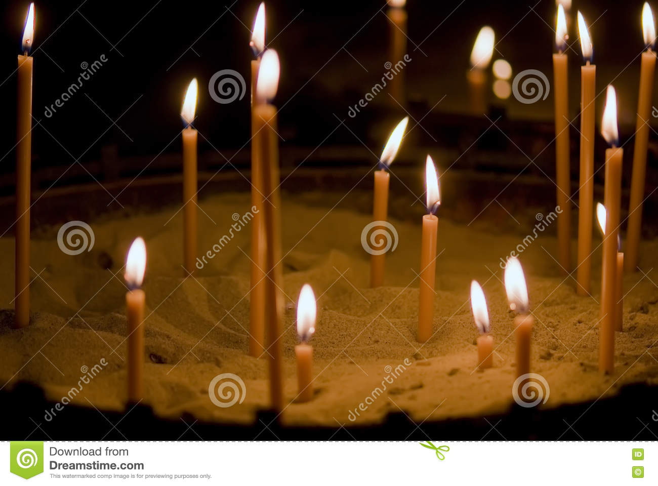 Burning candles in the sand