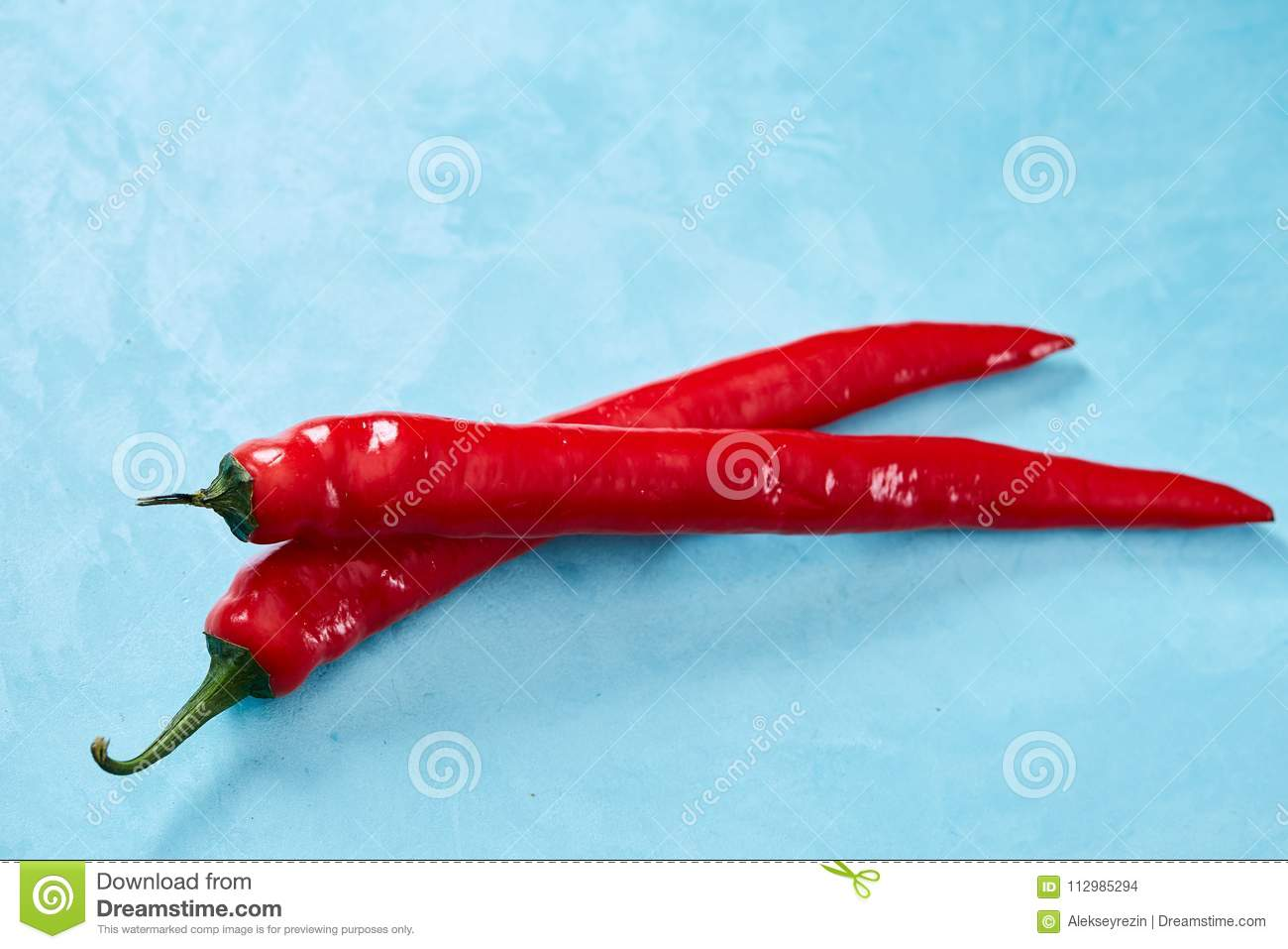 Burning fresh red hot pepper on a blue background, top view, close-up