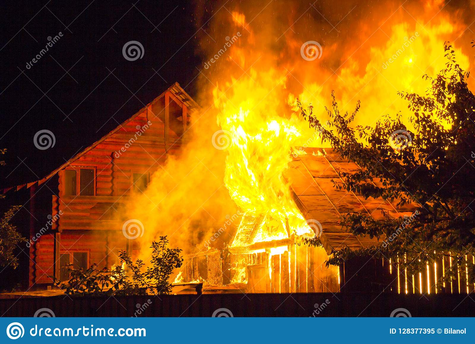 Burning wooden house at night. Bright orange flames and dense sm