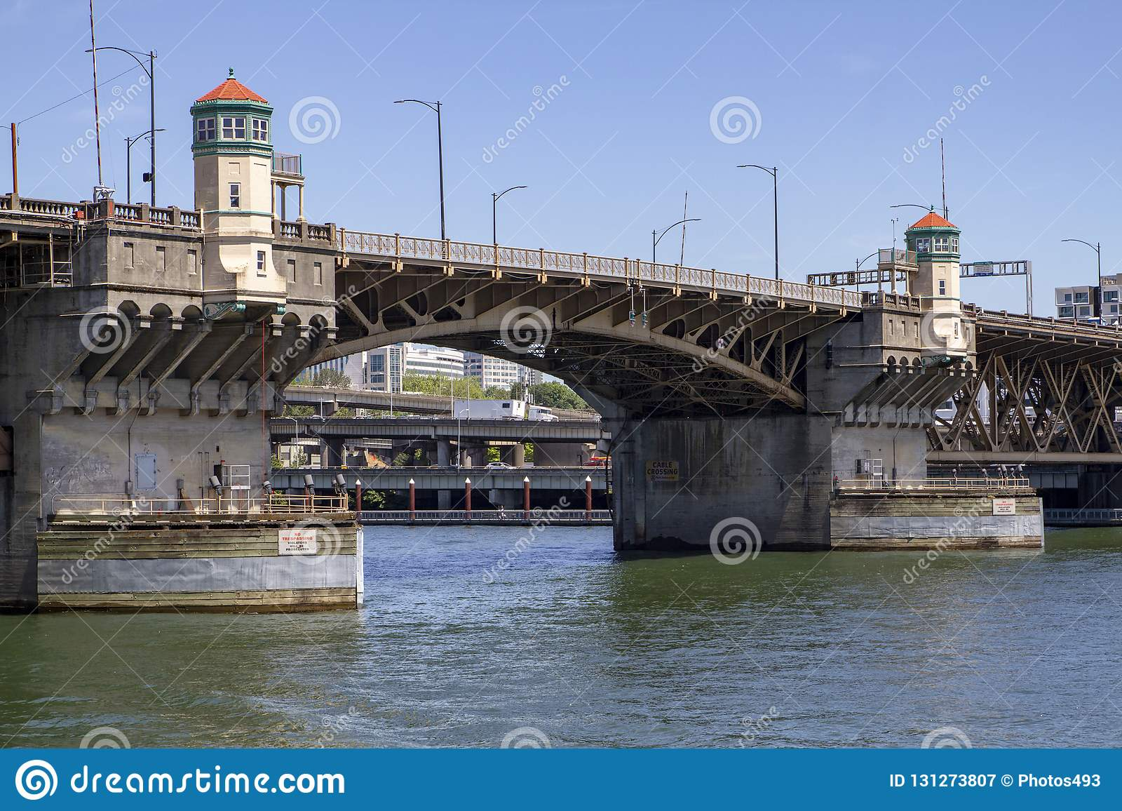 Burnside Bridge over Willamette River in Portland Oregon on a sunny day with blue skies